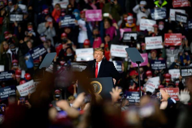 Donald Trump standing in front of a crowd: U.S. President Donald Trump speaks at a campaign rally at North Coast Air aeronautical services at Erie International Airport on October 20, 2020 in Erie, Pennsylvania. Trump is holding the rally two days ahead of the final presidential debate.