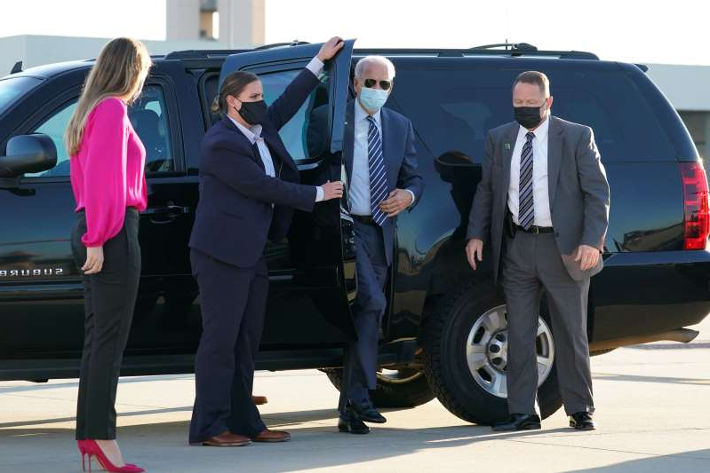 In this Oct. 18, 2020, photo, Democratic presidential candidate former Vice President Joe Biden steps out to board his campaign plane at Raleigh-Durham International Airport in Morrisville, N.C., en route to Wilmington, Del., as granddaughter Finnegan Biden looks on, right. Biden's biggest challenge may begin the day after Election Day. If he wins, he'll have just over 10 weeks to set up a new government. After making President Donald Trump's handling of the coronavirus pandemic a centerpiece of his campaign, Biden will have to show that his team can better handle the public health crisis.  (AP Photo/Carolyn Kaster)