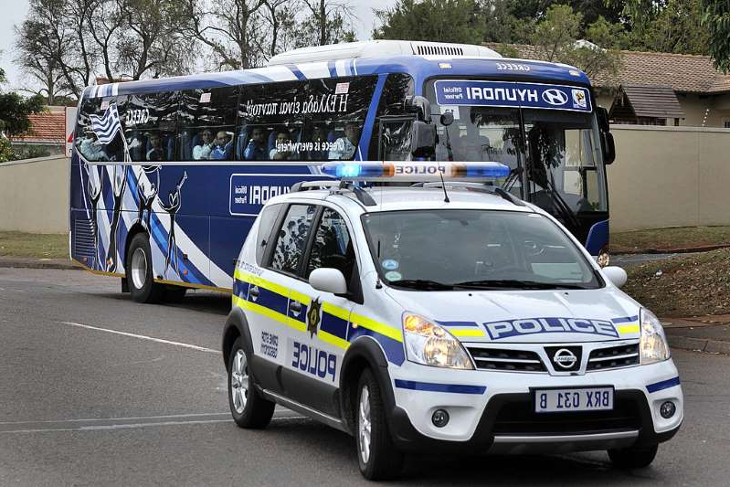 a blue bus driving down a street next to a car: Duban police car. South African authorities are investigating an attempted car hijacking at a busy city intersection.
