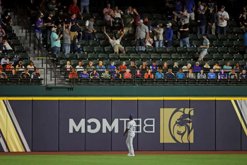 a crowd of people watching a baseball game: A fan catches the home run hit by Los Angeles Dodgers catcher Will Smith in the 6th inning against the Tampa Bay Rays in Game 2 of the 2020 World Series at Globe Life Field.