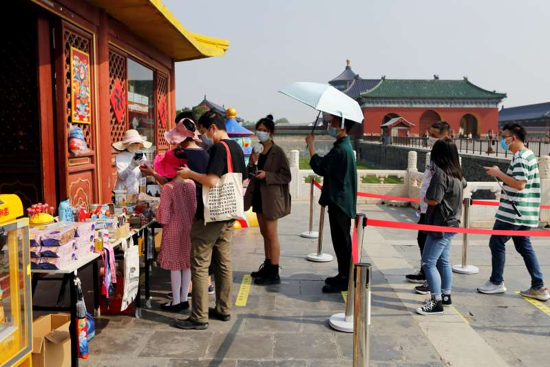 a group of people standing in front of a building: Visitors practise social distancing as they line up outside a souvenir shop at the Temple of Heaven in Beijing