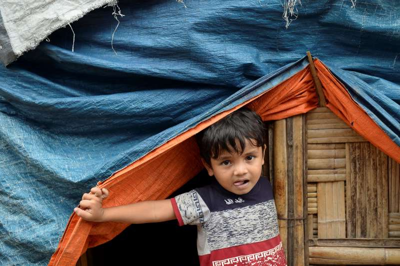 a little boy wearing a hat: A Rohingya refugee child peeps from his makeshift shanty at Kutupalong refugee camp, in Cox's Bazar. [File: Munir Uz Zaman/AFP]