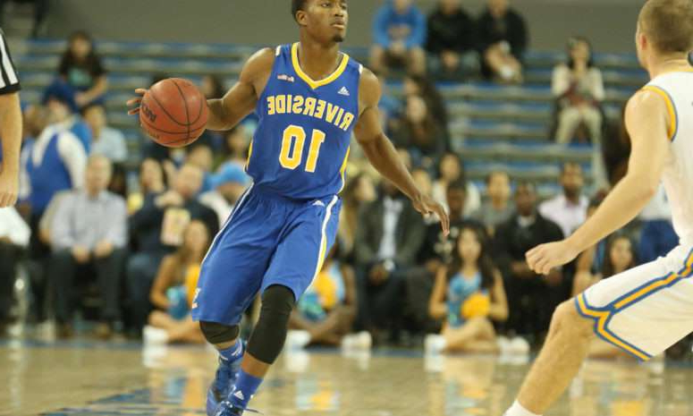 a man playing a game of basketball: A UC Riverside basketball player with the ball against UCLA.