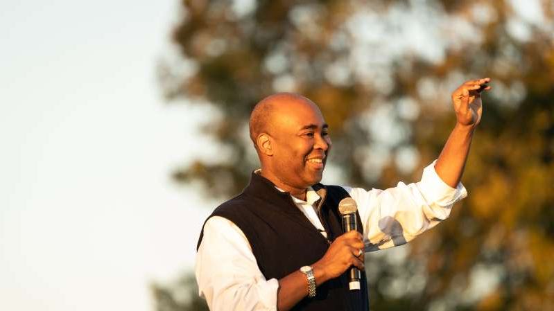 a man wearing a suit and tie: Democratic Senate candidate Jaime Harrison addresses supporters at a drive-in rally on October 17, 2020, in North Charleston, South Carolina.