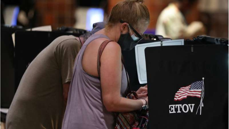 a person standing in front of a laptop: Millions of Americans have already cast their ballots in early voting