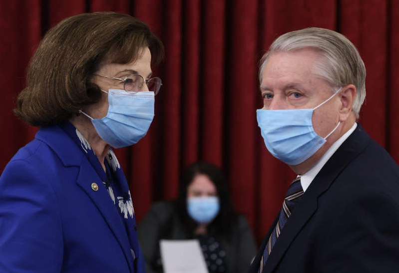 a person wearing a suit and tie: Sen. Lindsey Graham (L) (R-SC), Chairman of the Senate Judiciary Committee, speaks to ranking member Sen. Dianne Feinstein (R) (D-CA) prior to a committee hearing on September 24, 2020 in Washington, D.C.
