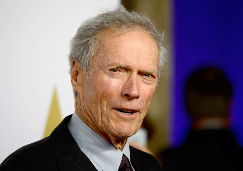 Clint Eastwood wearing a suit and tie smiling and looking at the camera: Director Clint Eastwood attends the 87th Annual Academy Awards Nominee Luncheon at The Beverly Hilton Hotel on February 2, 2015 in Beverly Hills, California.
