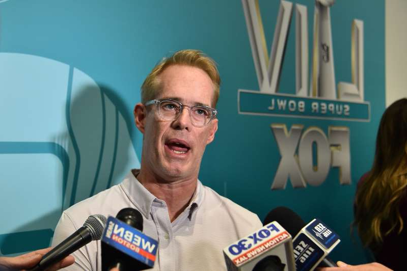 Joe Buck holding a sign: Joe Buck and broadcasting partner Troy Aikman discussed a military flyover prior to the Buccaneers-Packers game on Sunday.