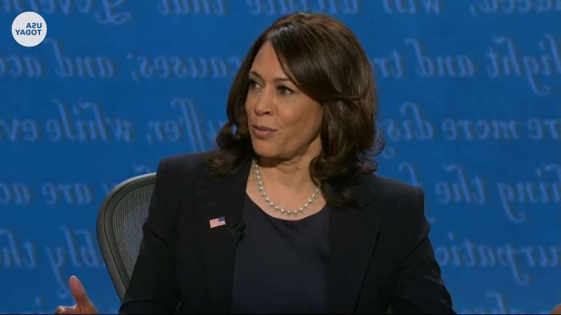 Kamala Harris holding a sign: Sen. Kamala Harris discusses her law enforcement and criminal justice record to Vice President Pence during the VP debate.