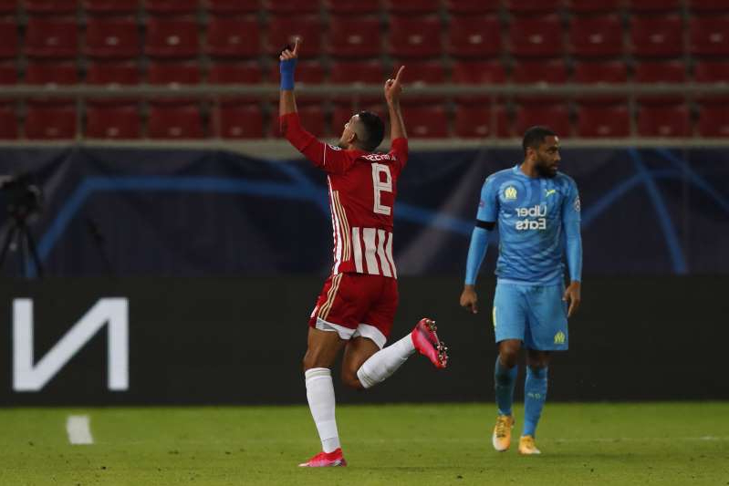 Olympiacos' Kouka, center, celebrates after scoring the opening goal against Marseille during the Champions League group C soccer match between Olympiakos and Marseille at Georgios Karaiskakis stadium in Piraeus port, near Athens, Wednesday, Oct. 21, 2020. (AP Photo/Thanassis Stavrakis)