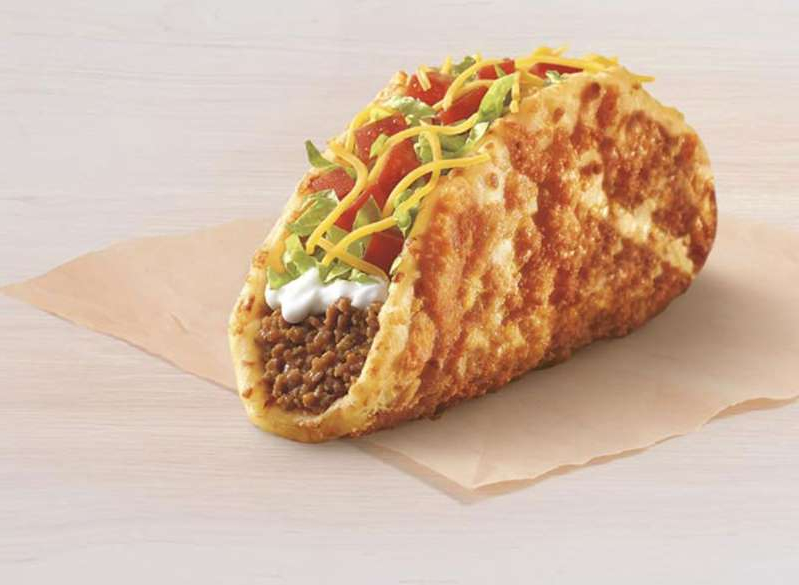 a cut in half sandwich sitting on top of a table: taco bell toasted cheddar chalupa