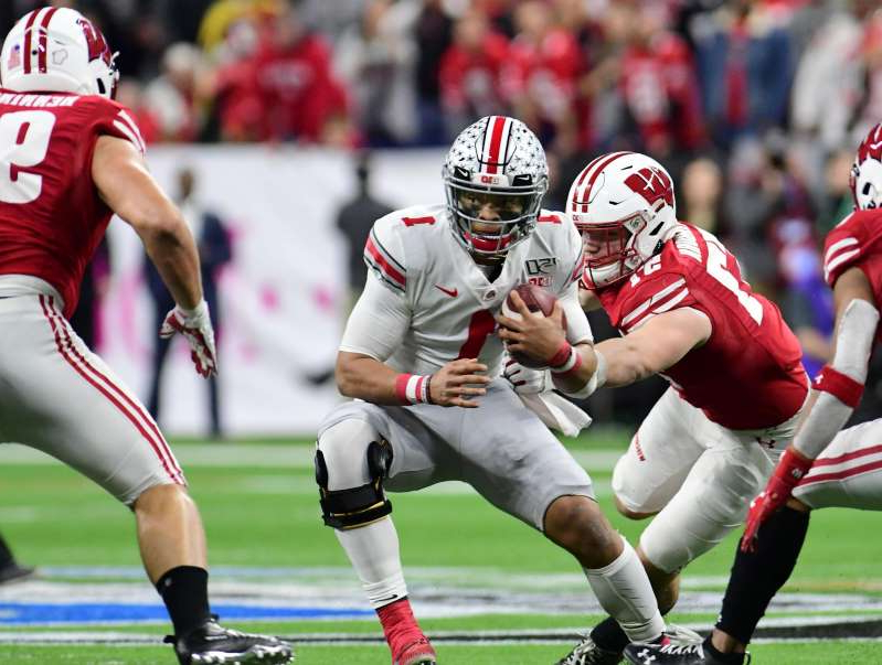 a group of baseball players playing a football game: Ohio State quarterback Justin Fields tries to avoid Wisconsin defenders during the first half in the 2019 Big Ten Championship Game at Lucas Oil Stadium.