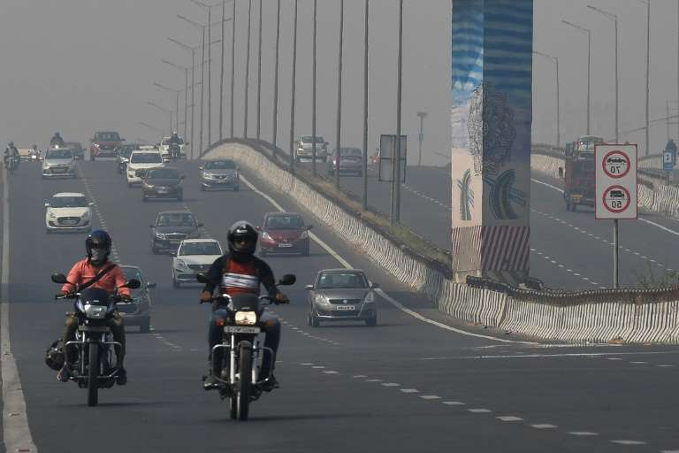a group of people riding motorcycles on a city street: Every winter the air in Delhi turns into a toxic soup