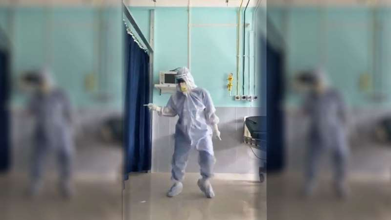"a person standing in front of a building: Dr. Arup Senapati, an surgeon at Silchar Medical College in northeastern India dances to the hit song ""Ghungroo"" for his COVID-19 patients."