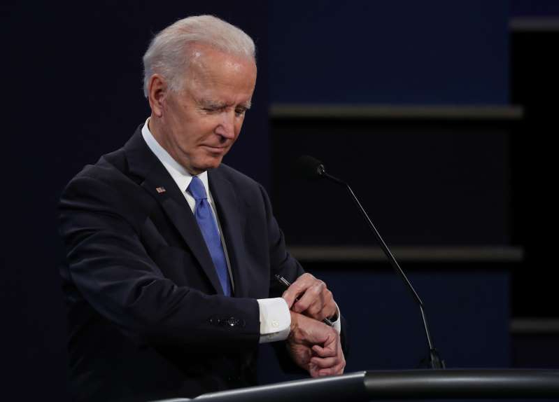 Joe Biden wearing a suit and tie: Democratic presidential nominee Joe Biden checks his watch during the final presidential debate against U.S. President Donald Trump at Belmont University on October 22, 2020 in Nashville, Tennessee.