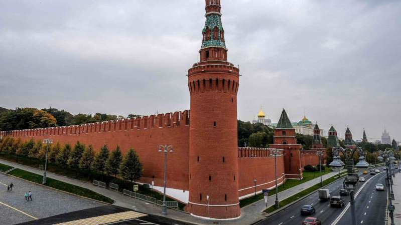 a castle with a clock on the side of a building: People walk near the Kremlin wall in central Moscow on Oct. 13, 2020.