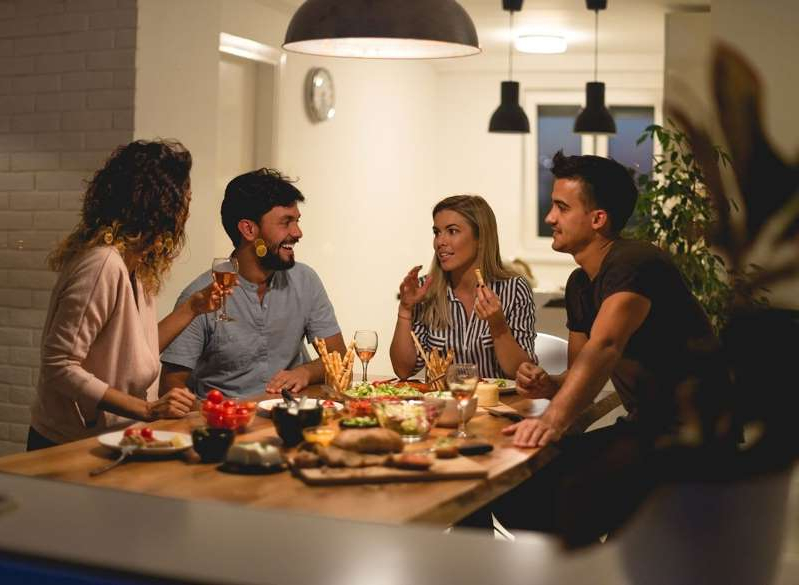 a group of people sitting at a table with food: dinner party