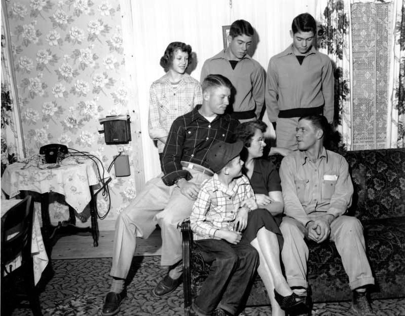 a group of people sitting posing for the camera: Mickey Mantle, 19, sensational Yankee rookie, chats with his family at their home in Miami, Okla., on April 12, 1951, the home where they lived after residing in Commerce. Left to right are, Father E.C. Mantle and his wife, Larry 10, and Mickey. Back, left to right are, twins Ray and Roy, 15, and Barbara, 13.