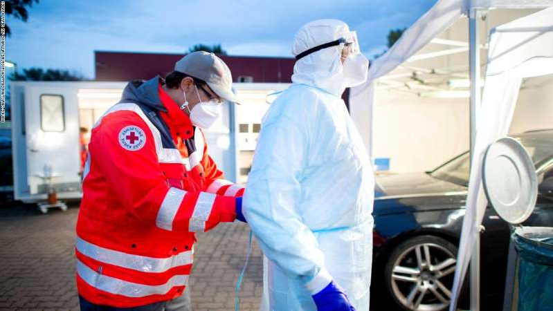 a man wearing a costume: Volunteers from the German Red Cross (DRK) prepare for patient smears in the Corona Drive-In test centre in the Empelde district. In the test centre of the DRK, people are tested at the behest of the public health department. Photo: Hauke-Christian Dittrich/dpa (Photo by Hauke-Christian Dittrich/picture alliance via Getty Images)