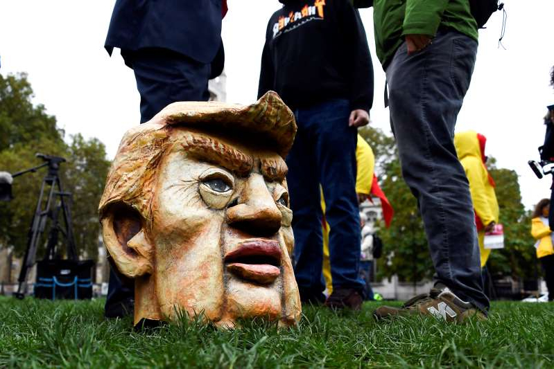 A mask of US President Donald Trump is seen in Parliament Square, as part of a day of action against the US trade deal, ten days before the US Presidential election, in London, Saturday, Oct. 24, 2020.  There will will be protests held nationwide against a proposed US trade deal, opposed by a number of organisations including Global Justice Now and Stop Trump Coalition. (AP Photo/Alberto Pezzali)