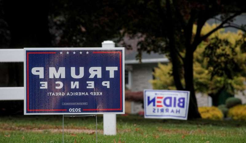 a sign on the grass: Campaign signs for President Donald Trump and Democratic nominee Joe Biden in Erie, Pa., October 20, 2020.