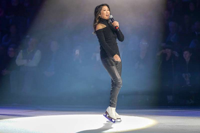 Kristi Yamaguchi riding a skate board in the dark