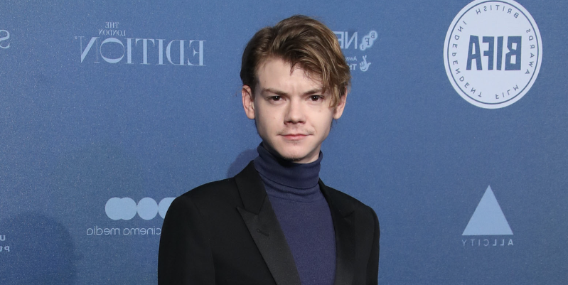 Thomas Brodie-Sangster holding a sign posing for the camera: Game of Thrones star Thomas Brodie-Sangster says he hasn't met anyone who liked the final season.