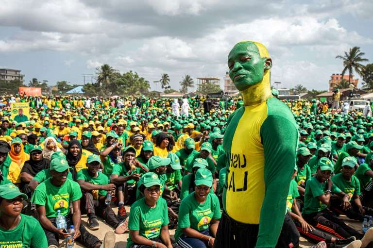 a group of people standing in front of a crowd: Supporters of the Tanzanian ruling party Chama Cha Mapinduzi gather at the Kibanda Maiti Stadium during the last campaign rally