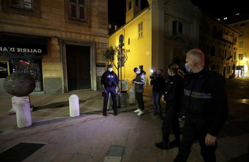 a group of people standing on a sidewalk: FILE PHOTO: Police officers check a person in Nice as the French Riviera city prepares for a new nightly curfew imposed in an effort to combat the the coronavirus