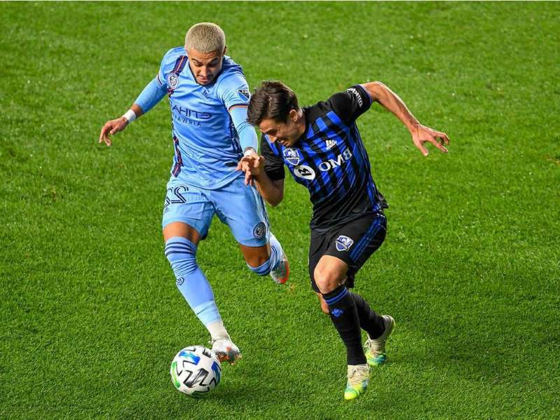 a group of young men playing a game of football: New York City defender Ronald Matarrita (22) and Montreal Impact forward Bojan Krkic (9) battle for the ball during the first half of the match between the New York City and the Montreal Impact at Yankee Stadium on Saturday, Oct. 24, 2020, in New York.