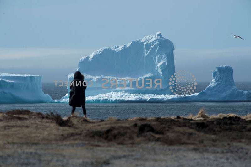 a man standing in front of a beach: Resident views the first iceberg of the season as it passes the South Shore of Newfoundland