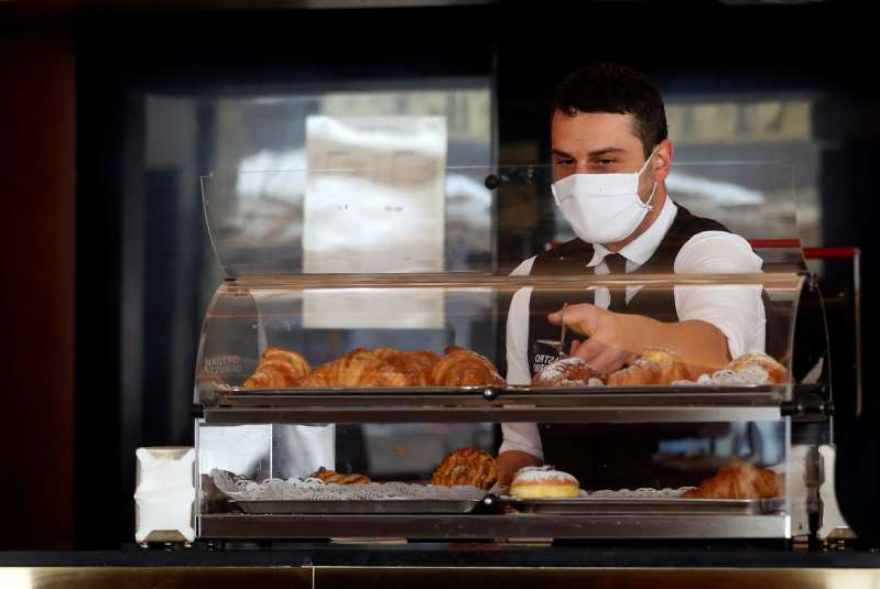 A waiter wears a mask while working Sunday at a bar in Rome.
