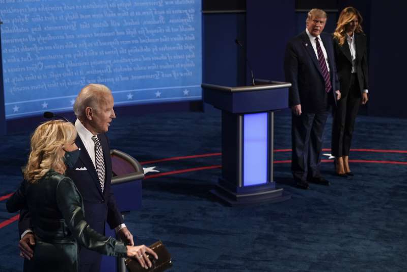 Donald Trump standing next to a man in a suit and tie: First lady Melania Trump, President Donald Trump, Democratic presidential candidate former Vice President Joe Biden and his wife Jill Biden, stand on stage following the conclusion of the first presidential debate at the Health Education Campus of Case Western Reserve University on September 29, 2020 in Cleveland, Ohio.