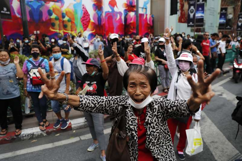 Pro-democracy protesters gather, flashing three-fingered salutes near a main shopping district in Bangkok, Thailand, Sunday, Oct. 25, 2020. Thailand's government and the country's pro-democracy movement appeared no closer to resolving their differences Saturday, as the protesters' deadline for Prime Minister Prayuth Chan-ocha to step down came and went with no new action from either side, and no backing down.(AP Photo/Gemunu Amarasinghe )