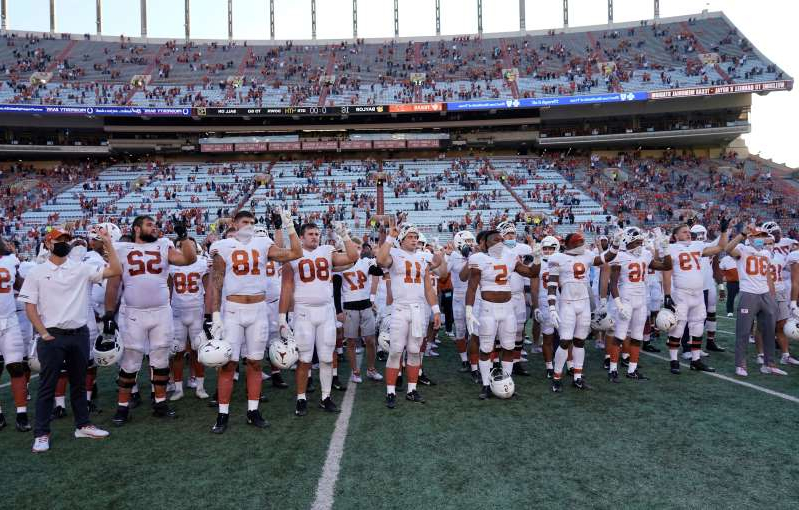 Texas players, including Sam Ehlinger (11), sing