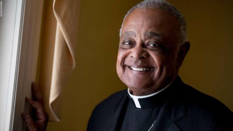 Wilton Daniel Gregory wearing a suit and tie smiling and looking at the camera: Archbishop Wilton Gregory poses for a portrait following mass at St. Augustine Church in Washington, DC on June 2, 2019.