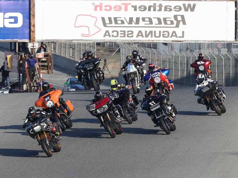 a group of people on a motorcycle in a parking lot: The sight of 14 race-prepped baggers going balls out toward turn 1 at Laguna Seca at the King of the Baggers debut was epic.