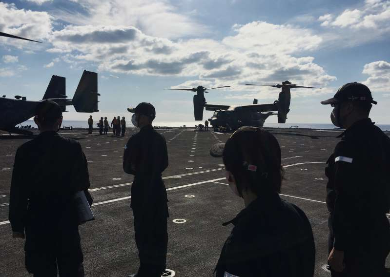 a group of people walking through a cloudy sky: Japan Maritime Self-Defense Force soldiers watch U.S. MV-22 Osprey aircrafts on board of the helicopter destroyer JS Kaga during Keen Sword, at mid-sea off south of Japan
