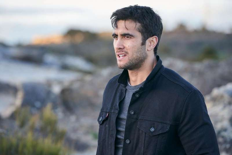 a man standing in front of a beach: Tane Parata in Home and Away