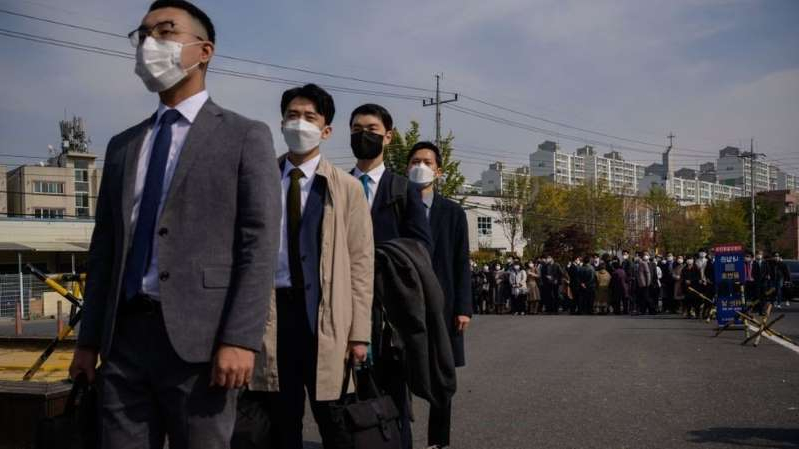 a man wearing a suit and tie standing in a parking lot: South Korean Jehovah's Witnesses arrive for work as conscientious objectors