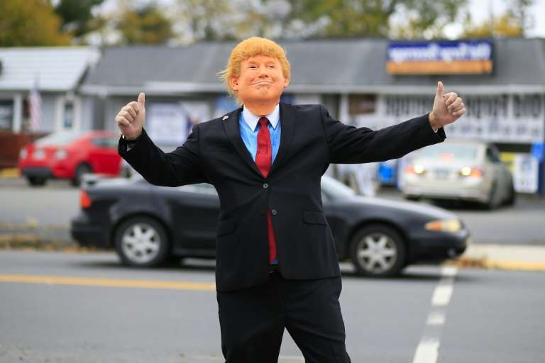 a man wearing a suit and tie walking down the street: Trump man -- In and around Scranton, Joe Biden's hometown, Republicans expect victory in the US election despite the polls