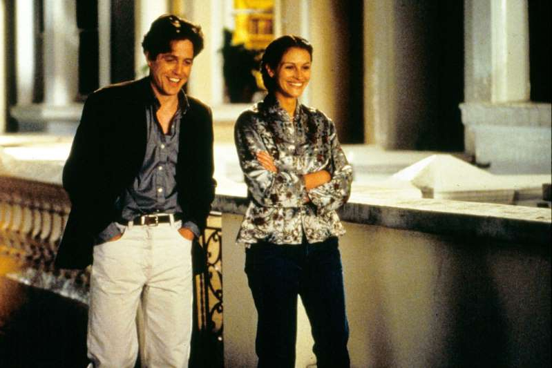 a person standing in front of a building: Moviestore/Shutterstock Julia Roberts and Hugh Grant in Notting Hill