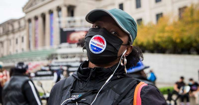 a person wearing a helmet: An early voter outside the Brooklyn Museum on Saturday. Pablo Monsalve/Corbis via Getty Images