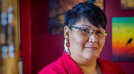 a person wearing glasses and smiling at the camera: Colleen Hele-Cardinal is the co-founder of the Sixties Scoop Network.