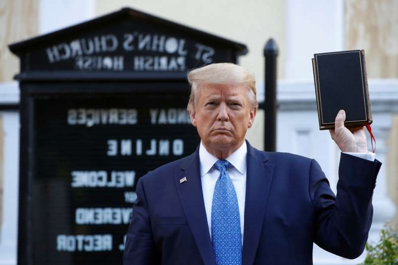 Donald Trump wearing a suit and tie: President Trump held a Bible outside St. John's Church across Lafayette Park from the White House on June 1 as federal authorities used tear gas to clear the area of peaceful protesters . (AP Photo/Patrick Semansky)