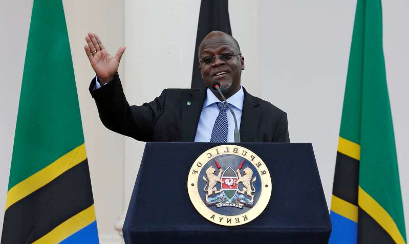 John Githongo wearing a suit and tie holding a sign posing for the camera: FILE PHOTO: Tanzania's President Magufuli addresses a news conference during his official visit to Nairobi