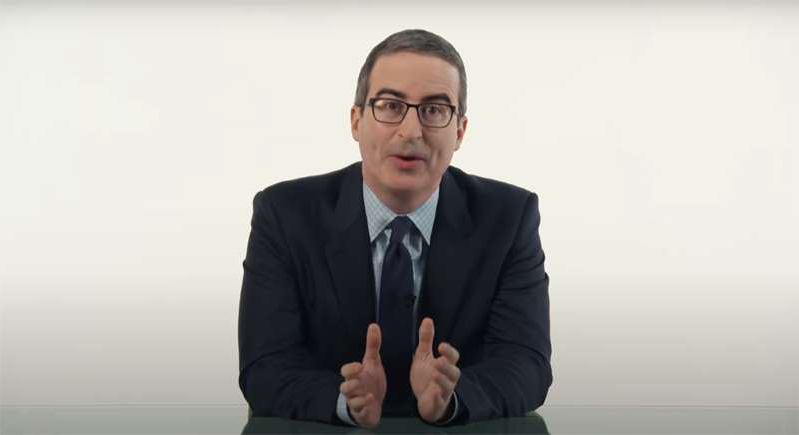 John Oliver wearing a suit and tie smiling at the camera