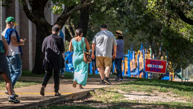 a group of people in a park: Voters approach the door at a polling location on October 13, 2020, in Austin, Texas. The first day of voting saw people waiting hours in line to cast their ballots.