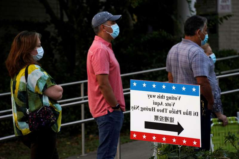 a group of people looking at a sign: People wait to vote in Houston on Oct. 13. (Go Nakamura/Reuters)