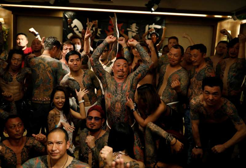a group of people standing in front of a crowd posing for the camera: The Wider Image: Breaking taboos: Japan's tattoo fans bare their ink